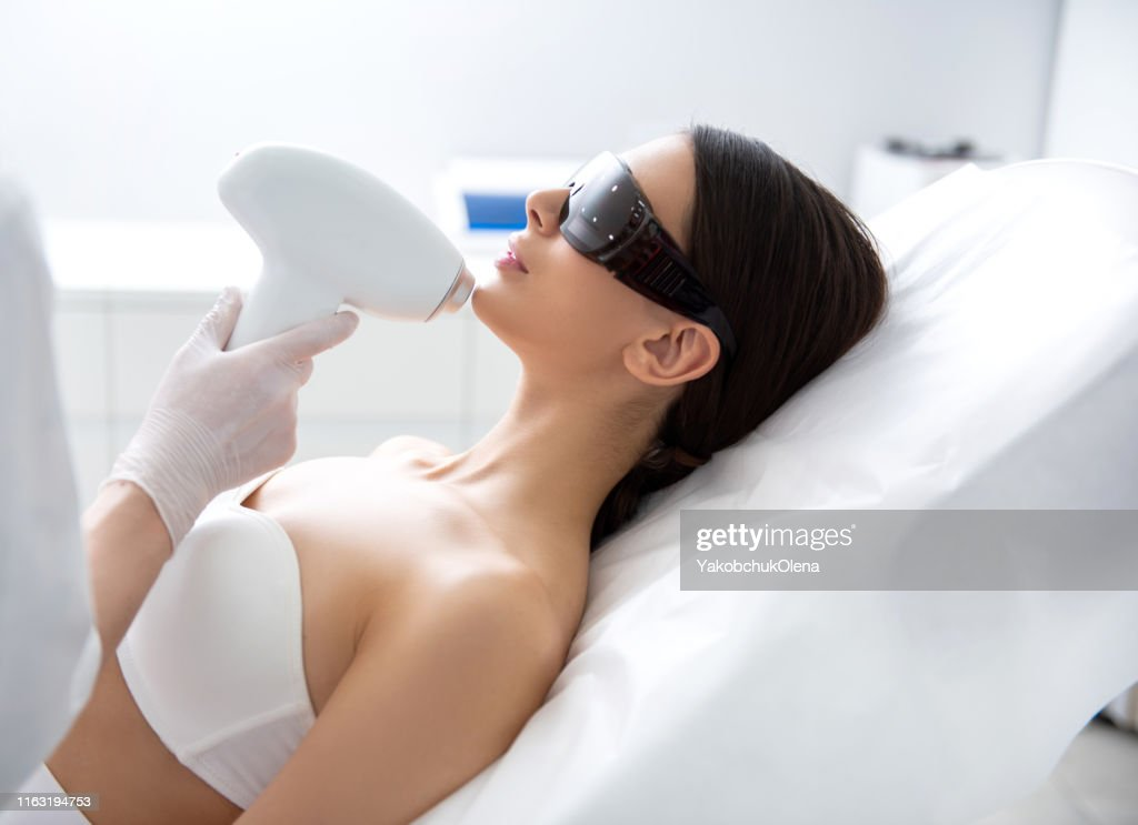 Young female on chin laser epilation procedure : Stock Photo