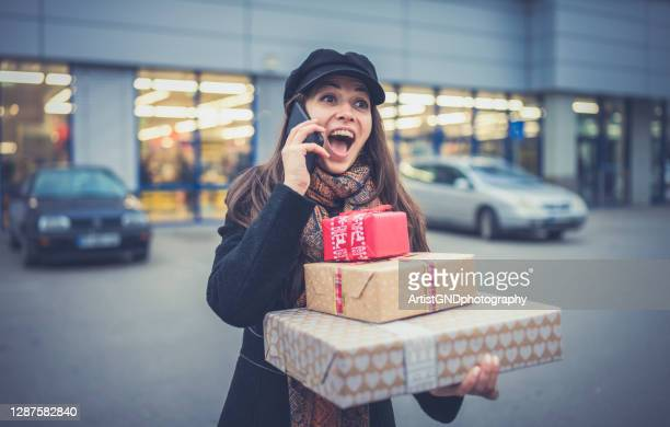 young female on christmas shopping talking on the phone. - boxing day stock pictures, royalty-free photos & images