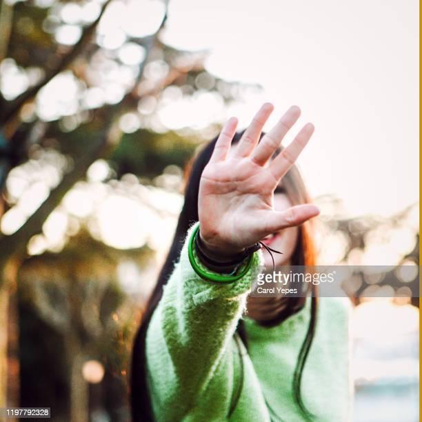 young female open palm.stop gesture - verteidigen stock-fotos und bilder