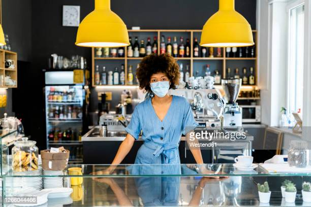 young female owner wearing mask standing at counter in coffee shop - small business stock pictures, royalty-free photos & images