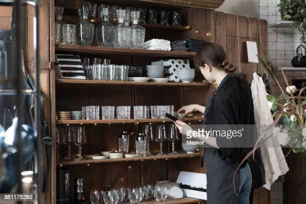 young female owner with digital tablet arranging rack at store - glas serviesgoed stockfoto's en -beelden