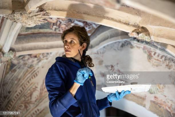 ung kvinnlig målare i mitten av återställa kyrkan målningar - stock photo - religiös symbol bildbanksfoton och bilder