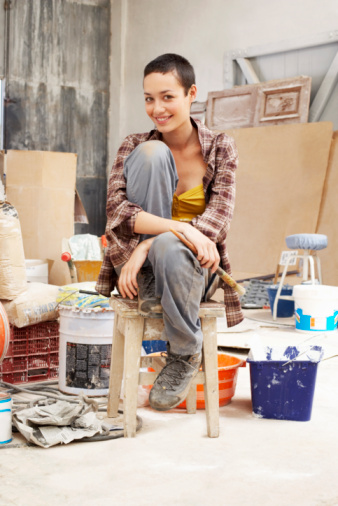 Young female Painter sitting in work site with equipment, portrait - gettyimageskorea