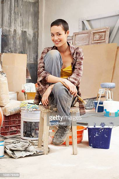 Young female Painter sitting in work site with equipment, portrait