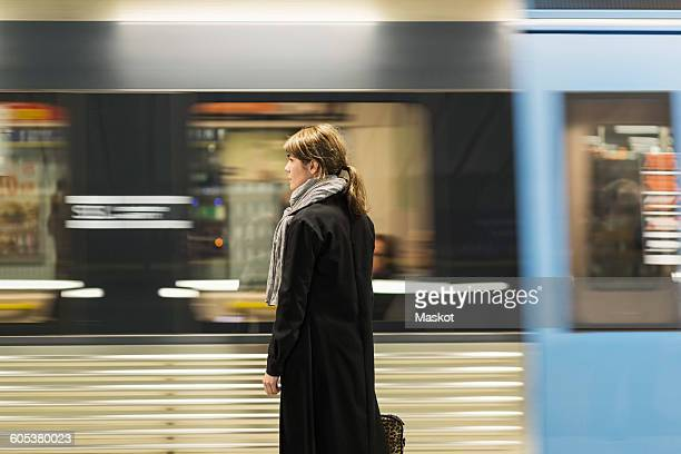 young female passenger standing at railroad station platform - subway platform stock pictures, royalty-free photos & images