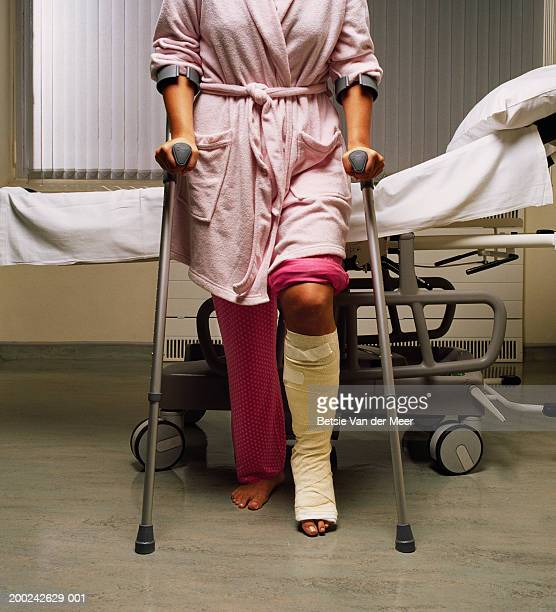Young female patient by hospital bed, using crutches, cast on leg