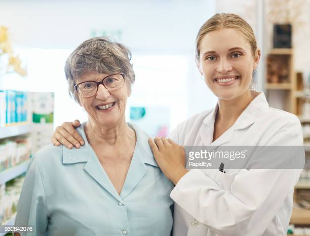 young female pharmacist gives senior woman customer a reassuring hug - compassionate eye stock pictures, royalty-free photos & images