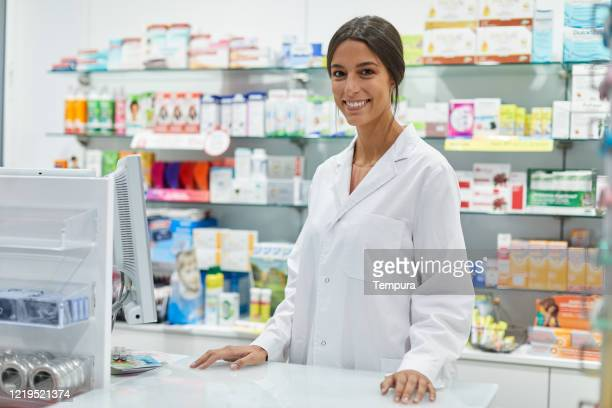young female pharmacist portrait looking at camera . - farmácia imagens e fotografias de stock