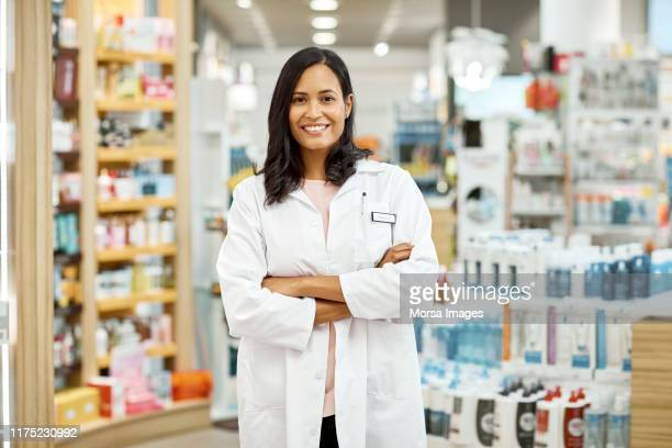 young female pharmacist standing with arms crossed - 薬剤師 ストックフォトと画像