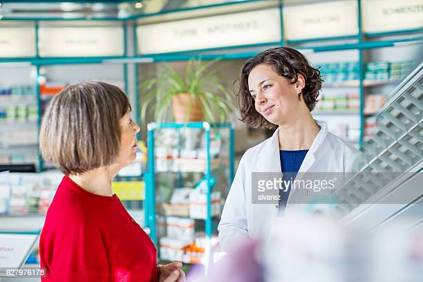 Young female pharmacist talking with senior customer