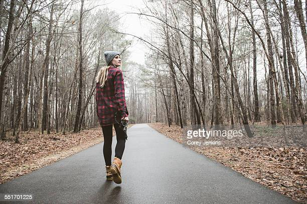 Young female photographer looking over her shoulder on rural forest road
