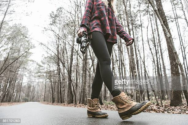 Young female photographer strolling on rural forest road