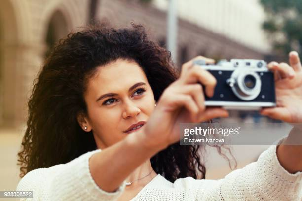 Young female photographer using a vintage camera
