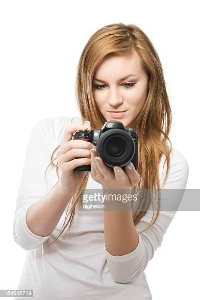 Young female photographer with DSLR on white background