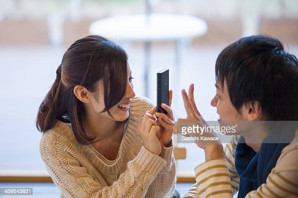 Young female photographing her boyfriend