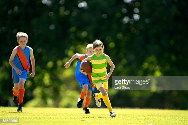 young female player running with ball - afl stock pictures, royalty-free photos & images