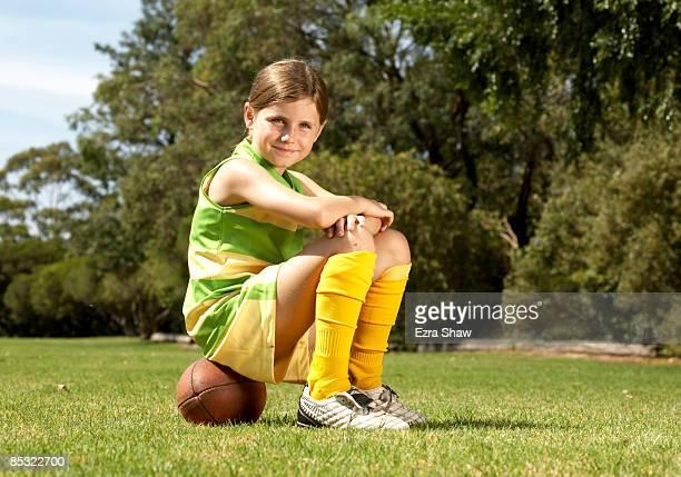 young female player sitting on a football - australian rules football stock-fotos und bilder