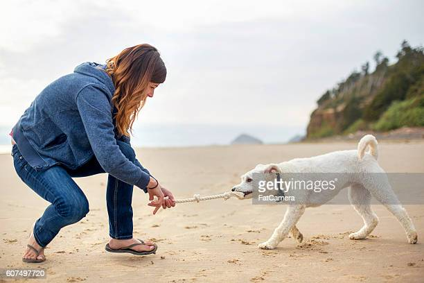 Young female playing tug-of-war with her dog