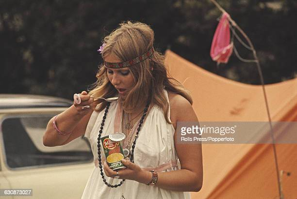 A young female pop fan wearing hippie style headband beads and smock dress eats from an open can of Del Monte pineapple chunks at the Isle of Wight...
