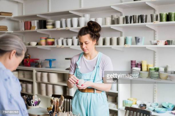 Young female potter holding clay with senior colleague against vases on shelf at workshop