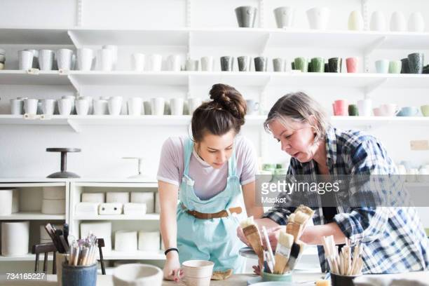 young female potter looking at mature artist molding clay at workshop - craft product stock pictures, royalty-free photos & images