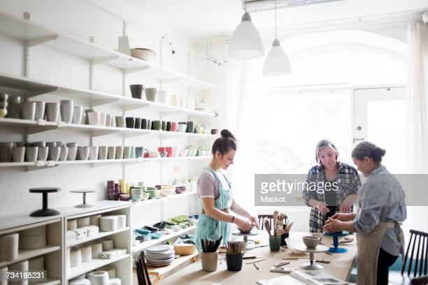 Young female potter working with colleagues at ceramics workshop