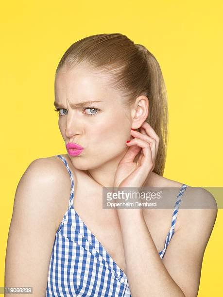 young female pouting with hand to face