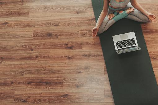 Young female practicing padmasana yoga pose alone 1135972930