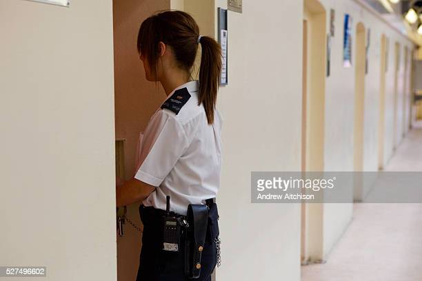 A young female prison officer checks the cells of each prisoner making sure everything is in order The Young Offenders Instution Aylesbury United...