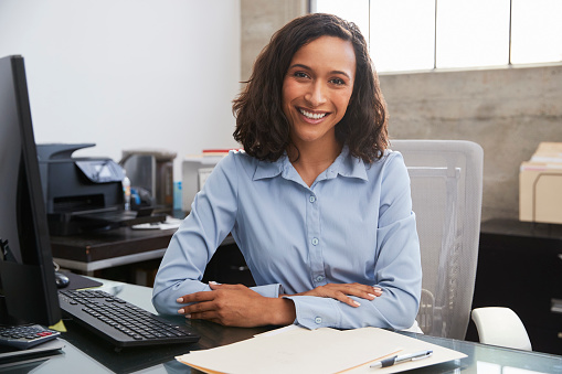 Young female professional at desk smiling to camera 1011793090