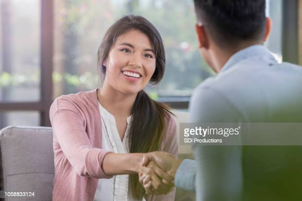 young female professional shakes hand with human resources representative - social grace stock pictures, royalty-free photos & images