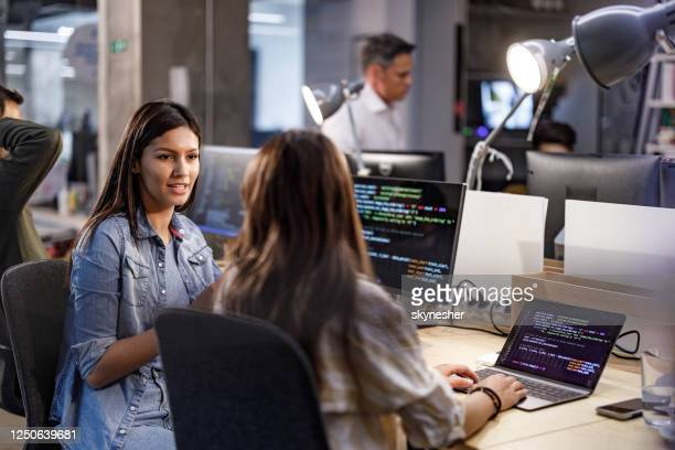 young female programmers talking in the office. - coding stock pictures, royalty-free photos & images