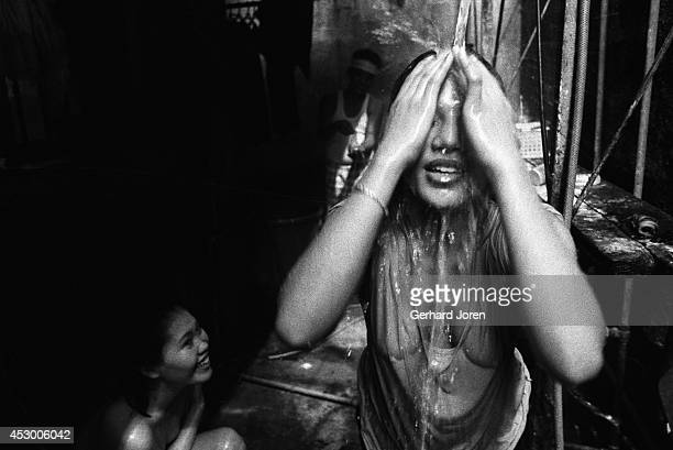 Young female prostitute takes a shower at the brothel where she works. The shower facilities are extraordinarily primitive, despite the high number...