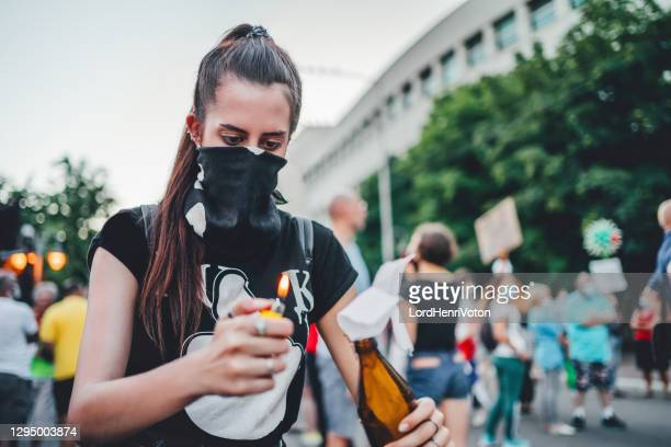 young female protester lights molotov cocktail - riot stock pictures, royalty-free photos & images