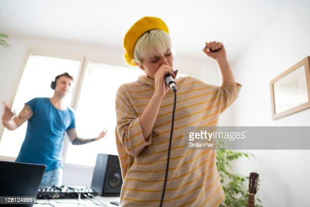 young female rapper rapping while the dj plays the music in home music studio - rapper stock pictures, royalty-free photos & images