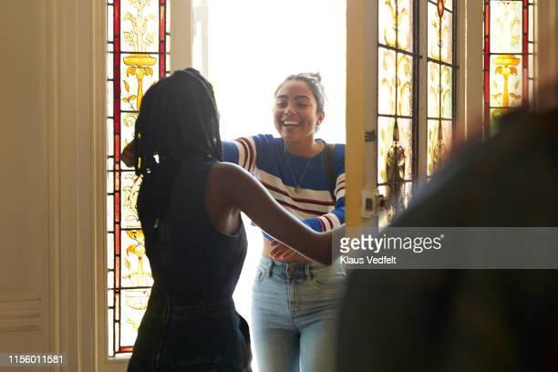 young female reaching to embrace friend - entrando fotografías e imágenes de stock