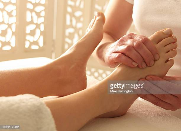 Young female receiving reflexology treatment
