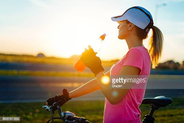 Young female recreational athlete drinking energy drink