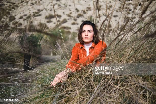 young female resting near bushy grass - オレンジ色のシャツ ストックフォトと画像