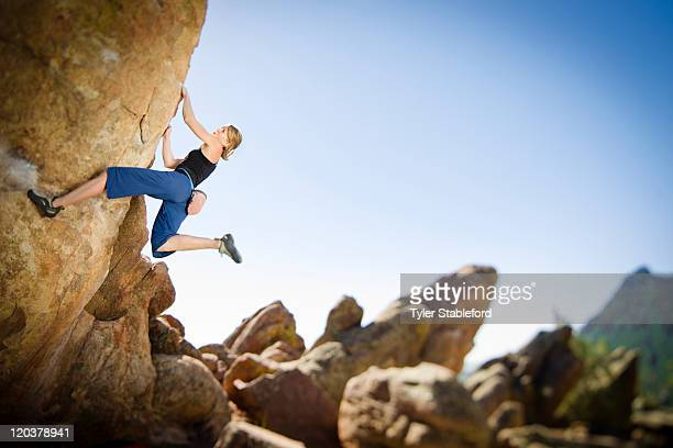 Young female rock climber bouldering.