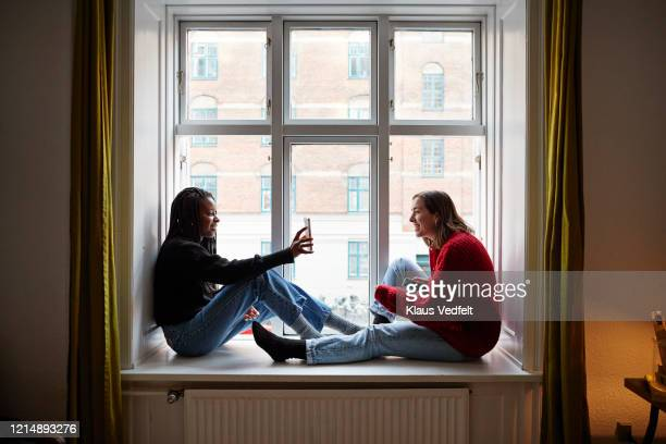 young female roommates using smart phones at apartment window - facebook friends stock pictures, royalty-free photos & images