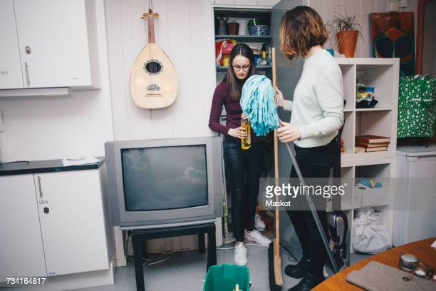 Young female roommates with cleaning equipment standing by closet in college dorm