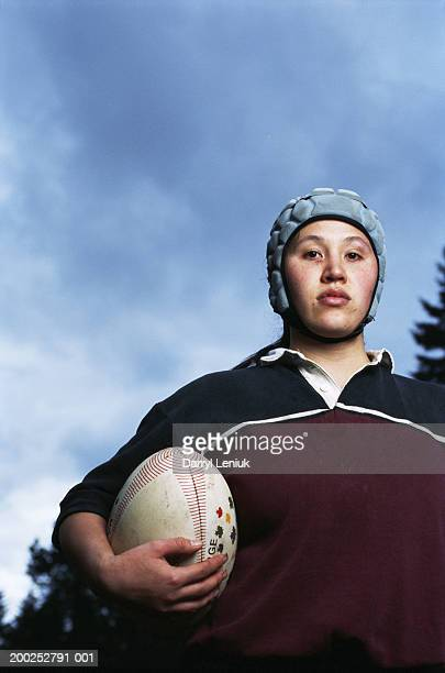 Young female rugby player holding ball, close-up, portrait