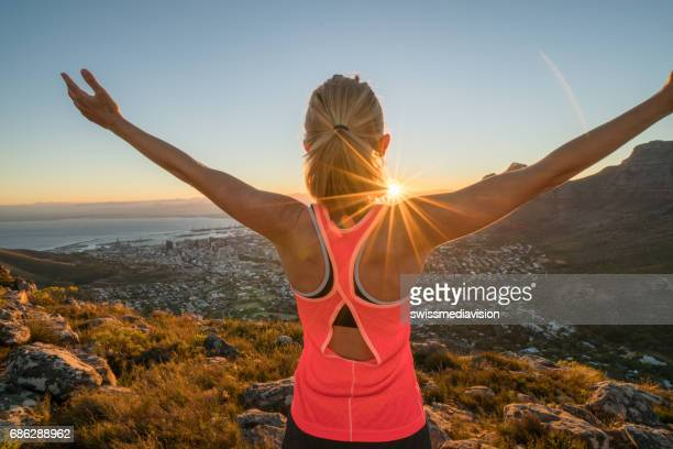 Young female runner arms outstretched at sunrise