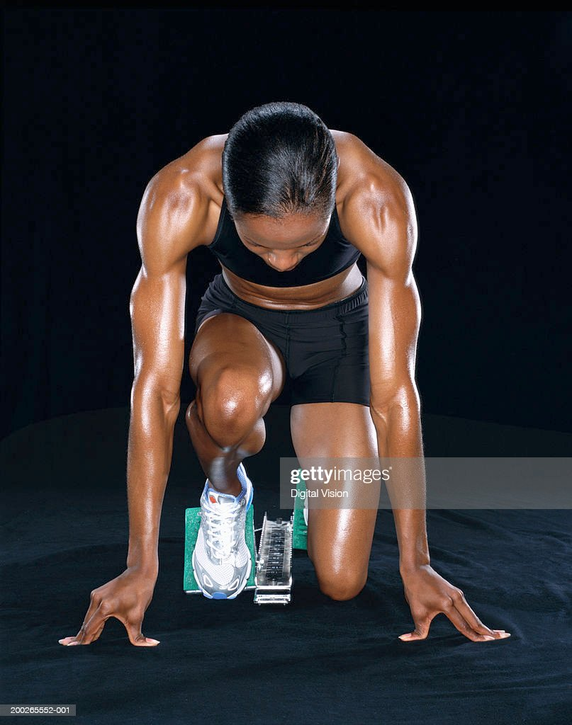 Young female runner at starting block : Stock Photo