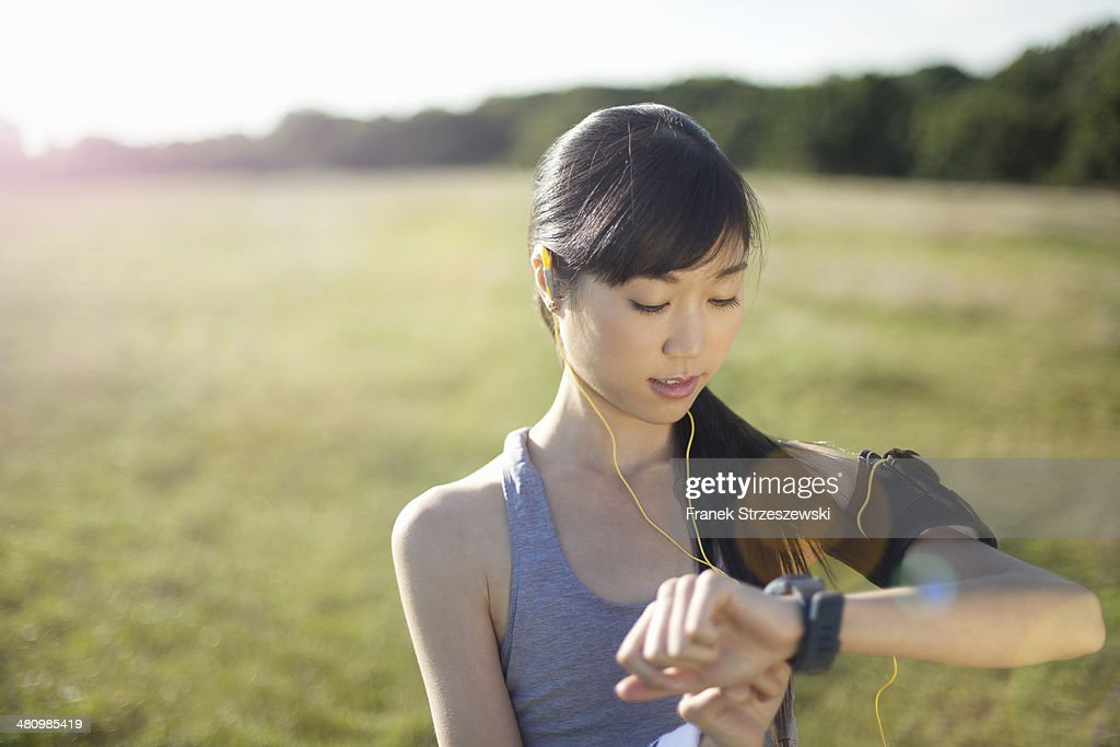 Young female runner checking watch for time : Stock Photo