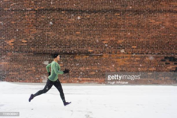 young female runner in knit hat running along snow covered sidewalk - peterborough ontario stock photos and pictures