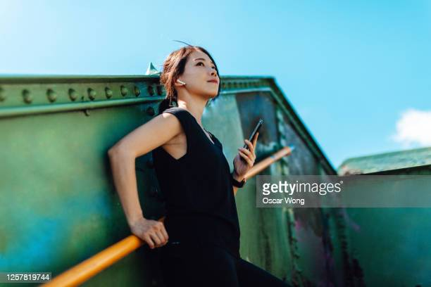 young female runner looks at the sky with smartphone on her hands in art district, city downtown - bright colour stock pictures, royalty-free photos & images