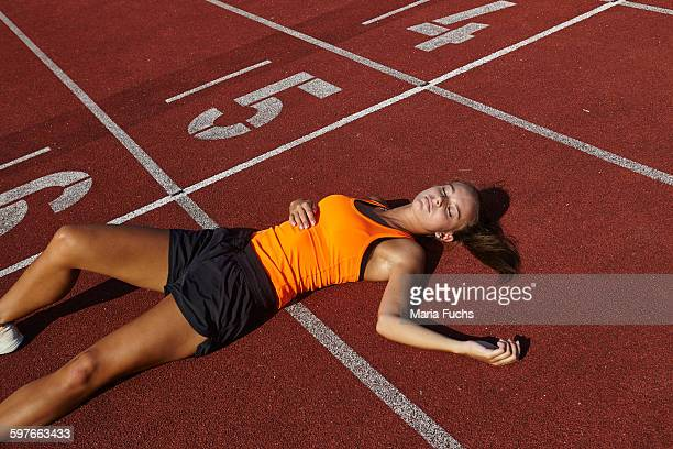 Young female runner lying on back exhausted on race track