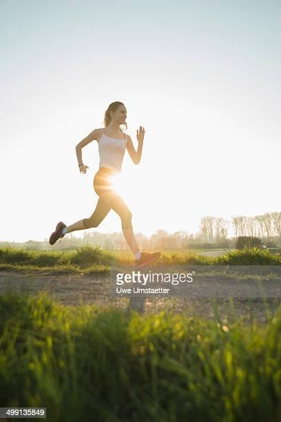Young female runner on sunlit dirt track